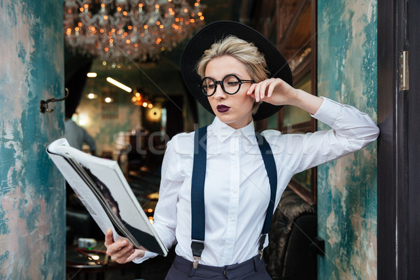 Concentrated young woman standing and reading magazine in cafe Stock photo © deandrobot