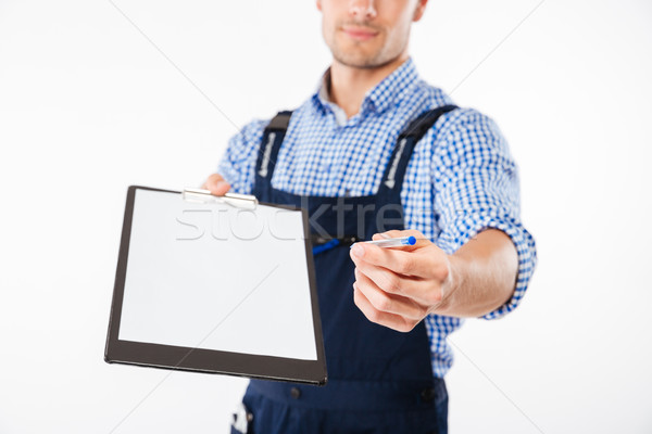 Cropped image of smiling builder giving blank sheet on clipboard Stock photo © deandrobot