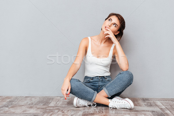Casual happy wondering woman sitting on the floor Stock photo © deandrobot