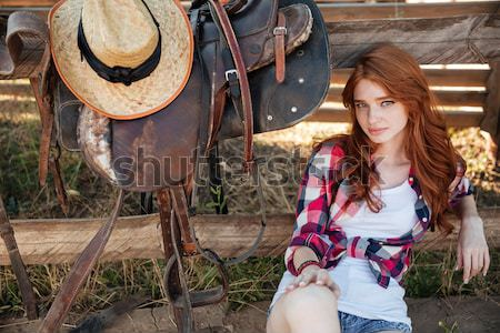 Stock photo: Cheerful cute redhead cowgirl resting at the ranch fence