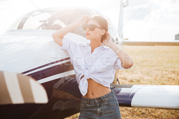 Woman in sunglasses standing outdoors near small plane Stock photo © deandrobot