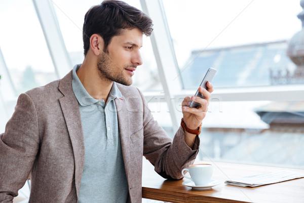 Férfi kabát sms chat üzenet okostelefon ül Stock fotó © deandrobot