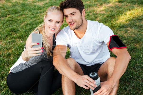 Sport man and woman making selfie in park after jogging Stock photo © deandrobot