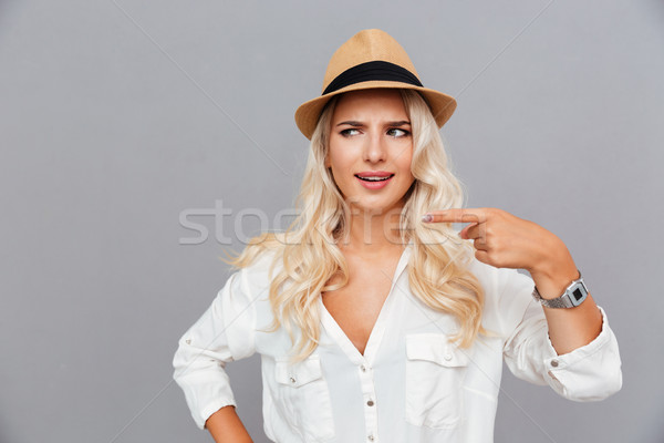 Unconfident embarrassed young woman pointing finger away Stock photo © deandrobot