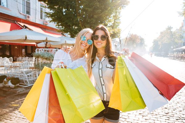 Two young women with shopping bags walking on the street Stock photo © deandrobot
