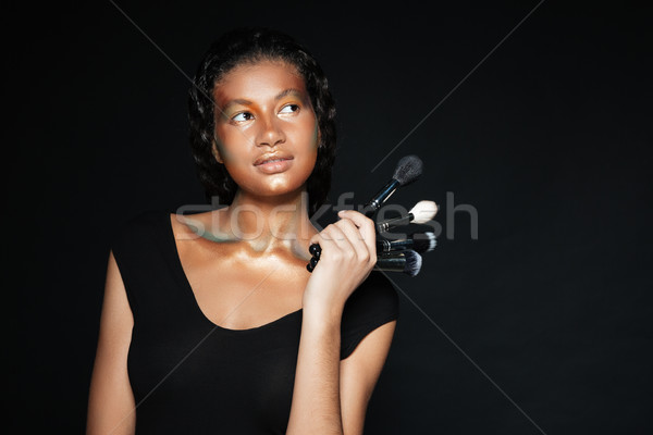 Pensive cute african american young woman holding makeup brushes Stock photo © deandrobot
