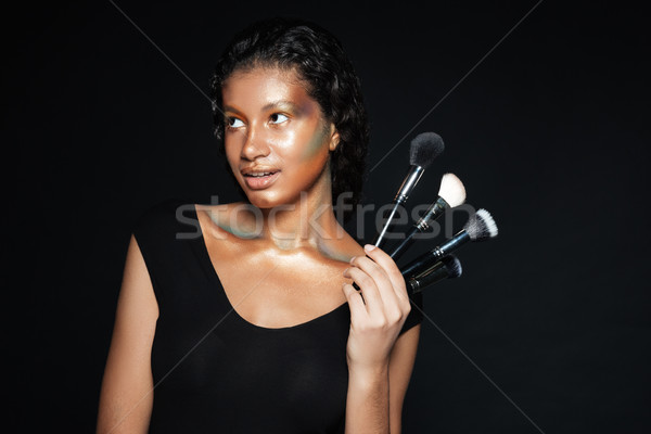 Stock photo: Smiling pretty african young woman standing and holding makeup brushes