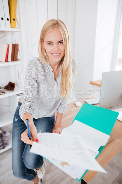 Woman giving sheet of paper to camera from a folder Stock photo © deandrobot