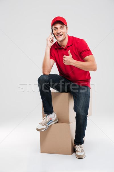 Jóvenes mensajero sesión cajas teléfono aislado Foto stock © deandrobot
