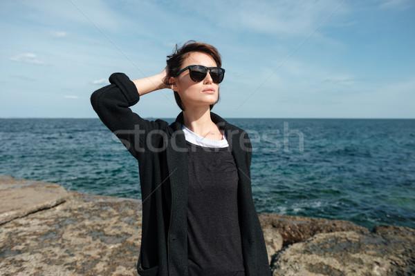 Vonzó fiatal nő napszemüveg sétál vízpart közelkép Stock fotó © deandrobot