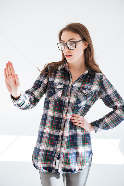 Serious young woman in glasses standing and showing stop gesture Stock photo © deandrobot