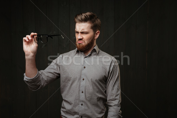 Portrait of an unsatisfied man in shirt looking at eyeglasses Stock photo © deandrobot