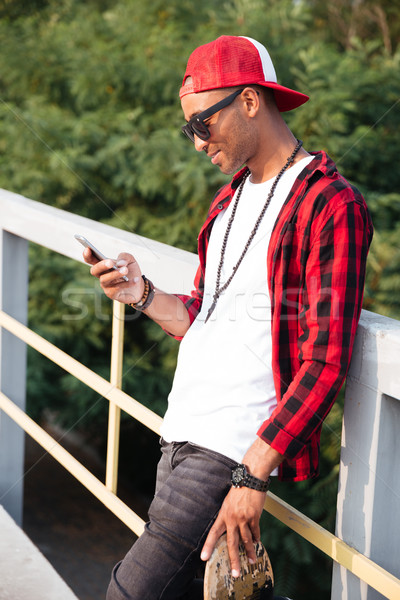 Cheerful dark-skinned man holding skateboard and looking at phone Stock photo © deandrobot