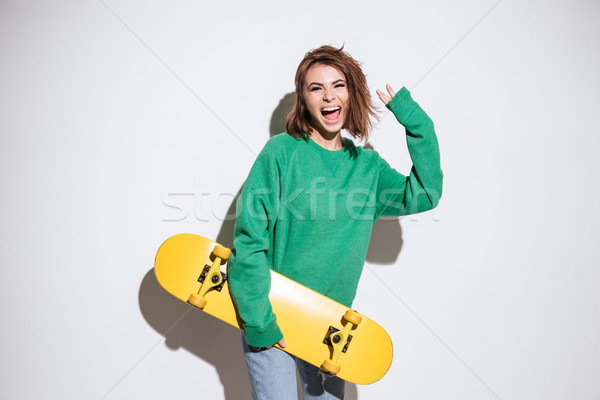 Happy skater lady with skateboard. Stock photo © deandrobot
