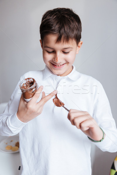 Happy little boy eating chocolate spread from jar by spoon Stock photo © deandrobot