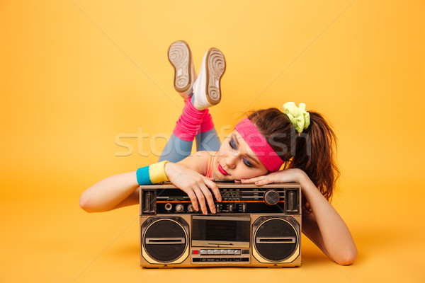 Cute young woman athlete lying and sleeping on retro boombox Stock photo © deandrobot