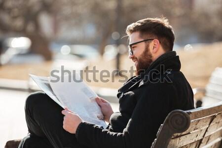 Komoly szakállas fiatalember ül olvas újság Stock fotó © deandrobot
