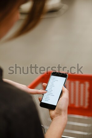 Cropped image of lady looking at list purchases in phone. Stock photo © deandrobot