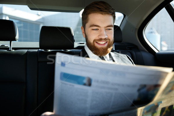 Pleased business man reading newspaper Stock photo © deandrobot
