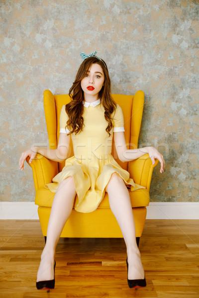 Vertical image femme séance fauteuil jaune Photo stock © deandrobot
