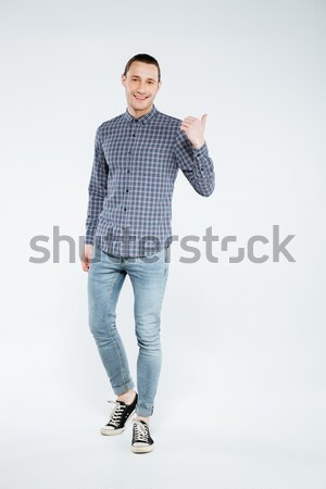 Vertical image of smiling man in shirt pointing away Stock photo © deandrobot