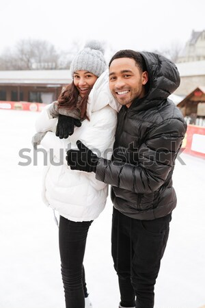 Cheerful loving couple skating at ice rink outdoors. Stock photo © deandrobot