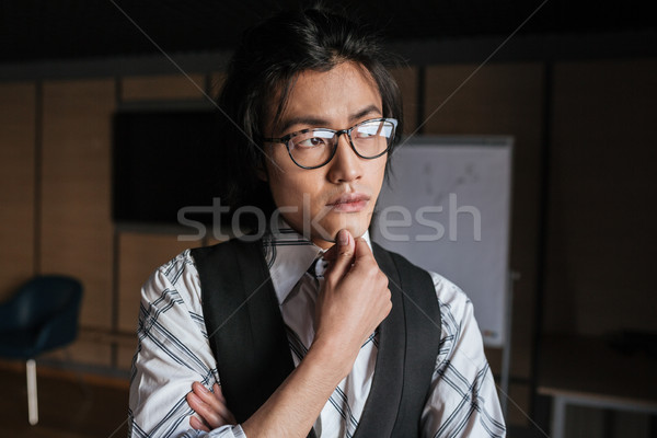 Handsome young asian man looking aside. Coworking concept. Stock photo © deandrobot