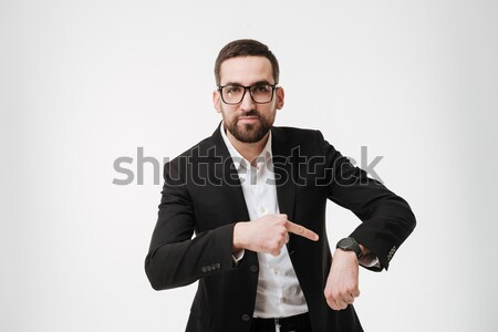 Serious young bearded businessman showing his watch. Stock photo © deandrobot