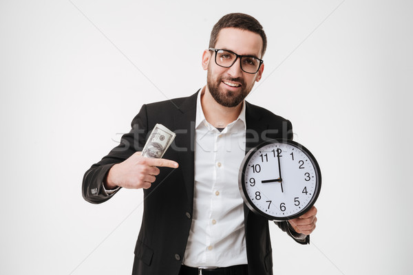 Bearded businessman holding money and pointing to watch. Stock photo © deandrobot