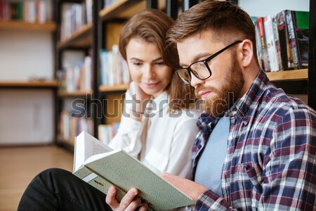 Happy young couple smiling and reading book Stock photo © deandrobot