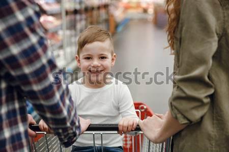 Happy boy in shopping trolley holding teddy bear Stock photo © deandrobot
