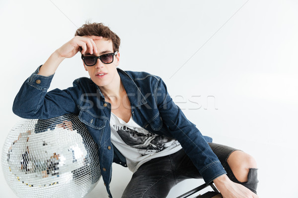 Young man near disco ball and boombox. Stock photo © deandrobot