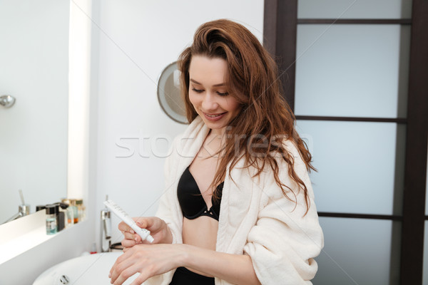 Woman taking care of hands and applying cream in bathroom Stock photo © deandrobot