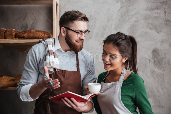 Happy loving couple bakers drinking coffee looking at notebook. Stock photo © deandrobot