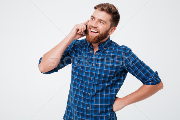 Happy bearded man in checkered shirt talking by the smartphone Stock photo © deandrobot