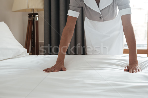 Cropped image of a chambermaid making bed in hotel room Stock photo © deandrobot