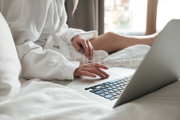 Cropped image of a woman in bathrobe on bed and using laptop Stock photo © deandrobot