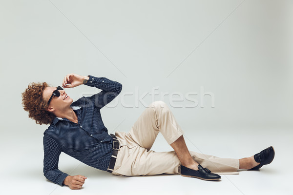 Handsome young retro man dressed in shirt lies on floor Stock photo © deandrobot