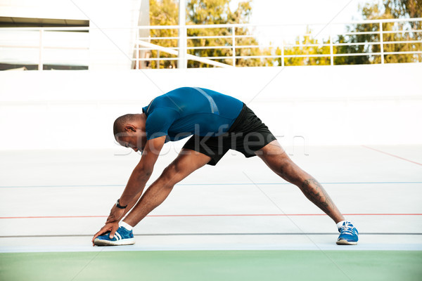Full length portrait of a motivated sportsman doing stretching Stock photo © deandrobot