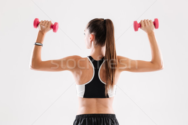 Back view portrait of a healthy slim sportswoman holding dumbbells Stock photo © deandrobot