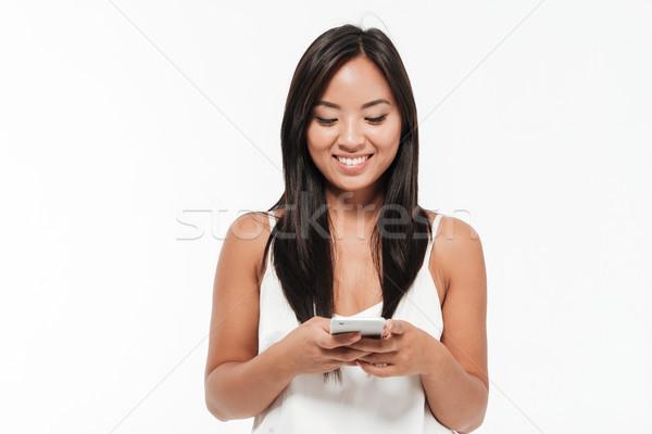 Stock fotó: Portré · mosolygó · nő · áll · mobiltelefon · mosolyog · fiatal
