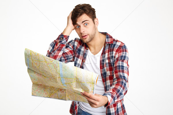 Portrait of a bewildered young man holding travel map Stock photo © deandrobot