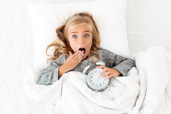 Top view of amazed blonde girl covering her mouth with hand, lyi Stock photo © deandrobot
