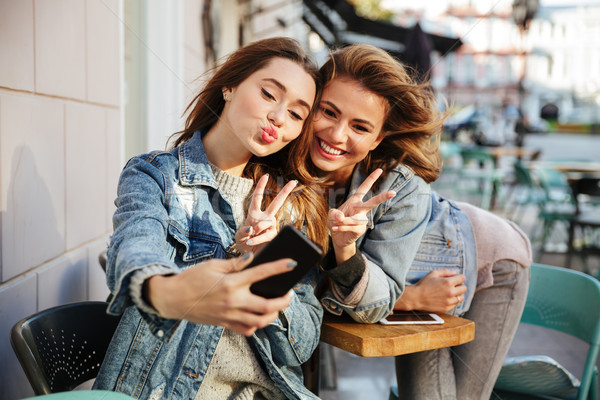 Close-up portrait of two beautiful young woman showing peace sig Stock photo © deandrobot