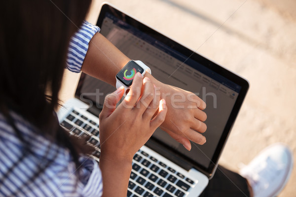 Close up top view portrait of woman using smart watch Stock photo © deandrobot