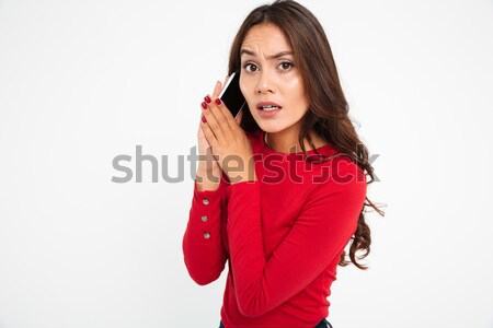 Portrait of a confused asian woman covers mobile phone Stock photo © deandrobot