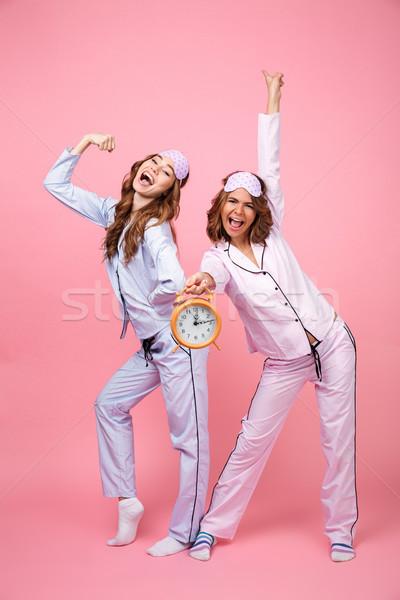Happy funny friends women in pajamas holding alarm clock Stock photo © deandrobot