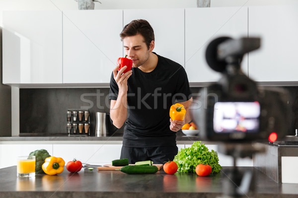 Attractive young man filming his video blog episode Stock photo © deandrobot