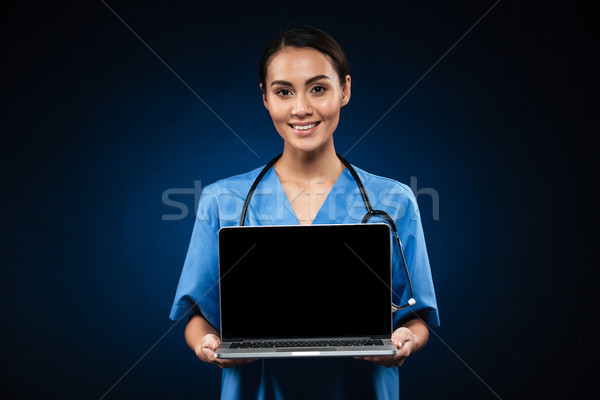 Young cheerful doctor showing blank screen of laptop computer isolated Stock photo © deandrobot