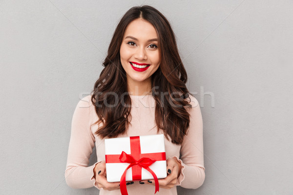 Stock photo: Pleased female 30s with red lips holding box gift-wrapped being